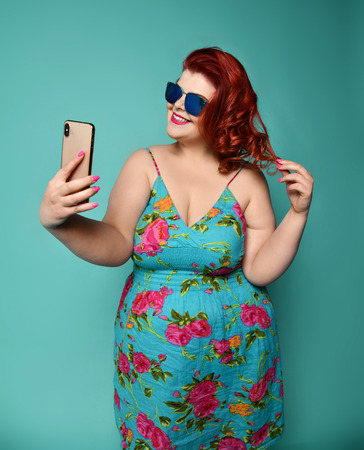 Pretty plus-size fat woman with hollywood smile in fashion sunglasses and colorful clothes does fashion selfie with pursed lips on mint background Reklamní fotografie