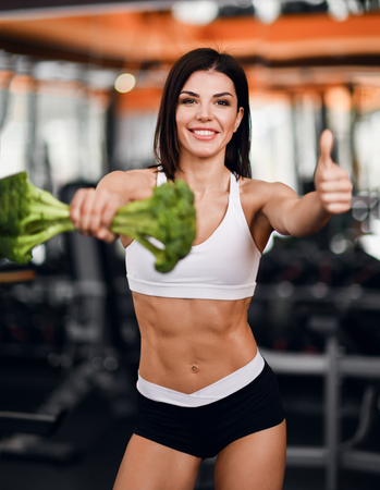 Diet and weight loss concept. Active athletic girl perfect body fitness instructor recommends healthy diet holding big broccoli and showing thumb up on background of gym equipment