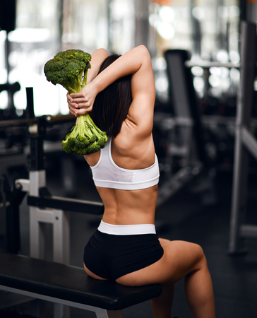 Diet and weight loss concept. Athletic woman fitness instructor sitting on gym bench working out triceps with big fresh broccoli as a weight dumbell on background of gym equipment