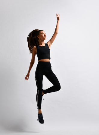 Happy sport girl working out in sportwear do jump exercises on white background