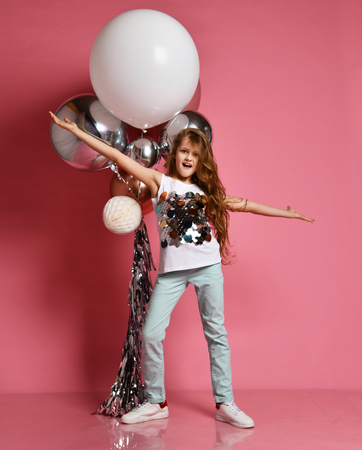 Young lady or teen girl in jeans and white shirt with her arms spreaded poses at fashion air balloons act like singer or pop star on pink background Reklamní fotografie