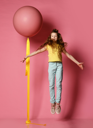 Smiling young teen girl in blue jeans and yellow t-shirt with her hands spread flying up the same as big helium balloon near her on pink background