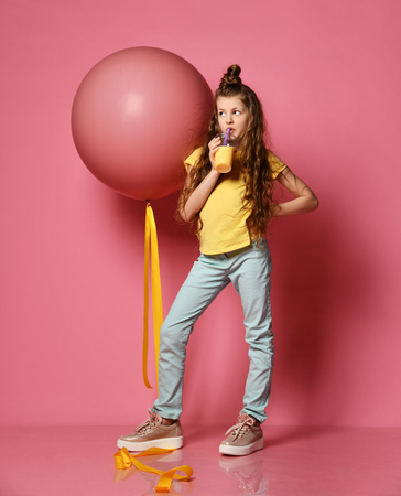 Cool and fashion teen girl in jeans and yellow t-shirt stepped on big pink balloon yellow tape, drinks yellow juice and looks somewhere up on pink background 版權商用圖片