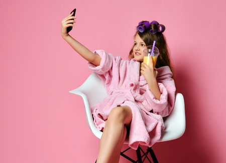Young lady teen girl in bathrobe and with hair in curlers in beauty shop drinks smoothie fresh juice and have fun taking cool selfie. Beauty concept on pink background with text copy space Stock Photo