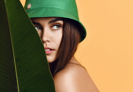 Beautiful young fashion girl with perfect skin in green hat hold tropical banana leaf in hands and covers a part of her face on yellow background Reklamní fotografie