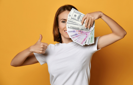 Smiling young woman in white t-shirt closes half of her face with a fan of banknotes cash and shows thumb up on yellow background