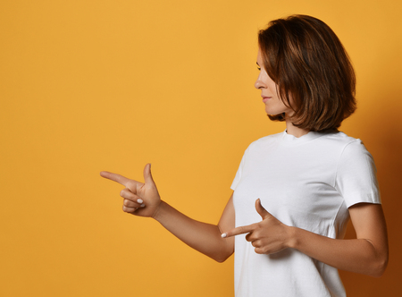 Young woman in white t-shirt and blue jeans shows finger-gun sign point her finger at free text space on yellow background
