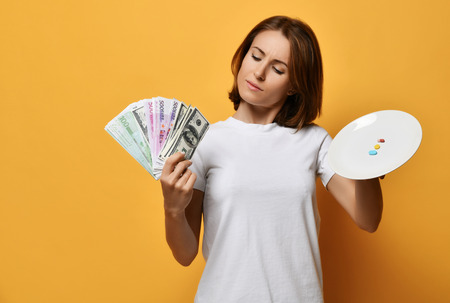 Woman compares makes choice between amount of different color tablet pills diet supplements drugs on plate and bundle of money dollars currency on yellow background