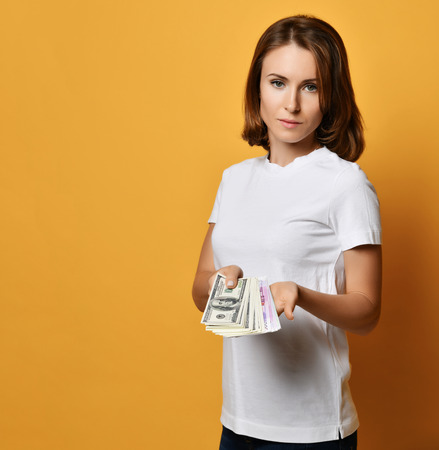 Young woman in white t-shirt and blue jeans holds shows us a bundle of money banknotes cash on her open palm on yellow background with free text copy space