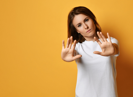 Woman in white t-shirt put her arms out like she is stopping something or somebody. Shows Stop sign gesture on yellow background with free text copy space Reklamní fotografie