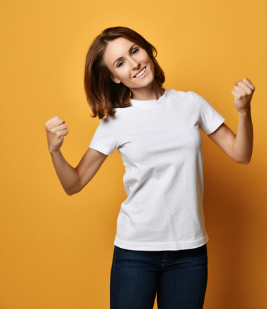 Happy smiling woman in white t-shirt and blue jeans shows clenched fist like she holds something on yellow background Reklamní fotografie