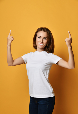 Young smiling woman in white t-shirt and blue jeans point fingers up at something free text copy space on yellow background