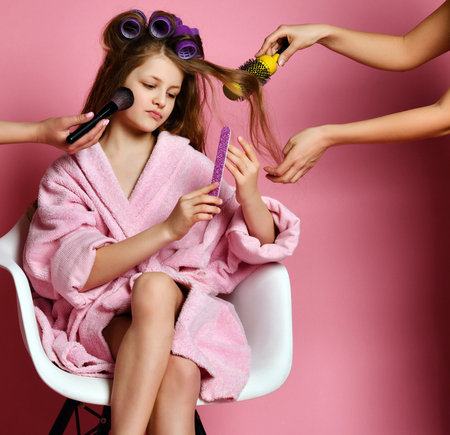 A bit dissatisfied young lady teen girl in spa salon makes hair style and manicure. Beauty concept on pink background