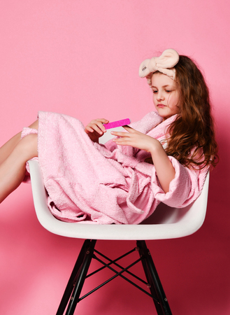 Young self-confident lady kid in bathrobe sits in fashion designer armchair and makes manicure on pink. Beauty concept on pink background Stock Photo