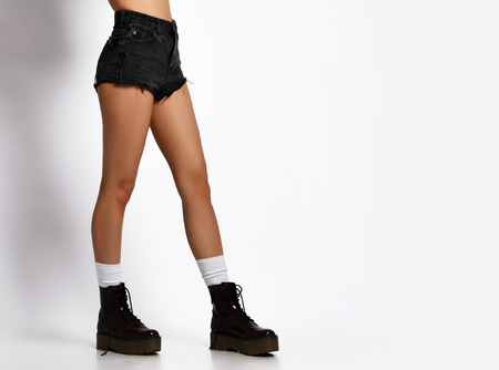Beautiful female legs wearing leather black boots in jeans designers shorts and dark green woman jacket walking jumping on white background Reklamní fotografie