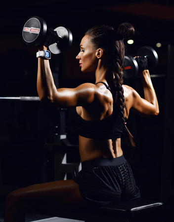 Young fitness woman working out with dumbbells weight in Gym. Diet and weight loss concept on dark background