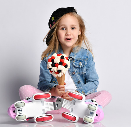 Baby girl kid in special roller skates sits on the floor and is surprised by a huge ice-cream in waffles cone with tasty topping marshmallows and berries Reklamní fotografie