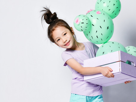 Young asian girl hold cactus balloon in pastel pink and purple flower box made of green round balloons with pink flowers. Creative idea minimal concept on gray background