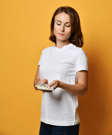 Young woman in white t-shirt and blue jeans looks at a bundle of money banknotes cash she holds and going to count it on yellow background