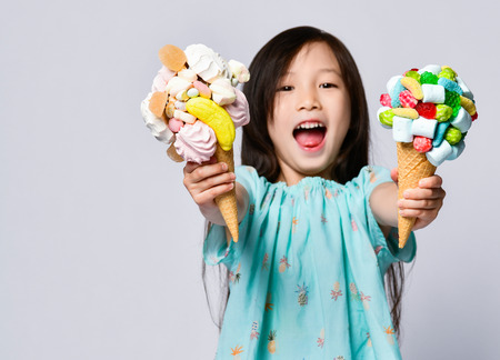 Baby girl kid eating two sweet big ice-cream in waffles cones with tasty raspberry marshmallow marmalade happy smiling on pink background