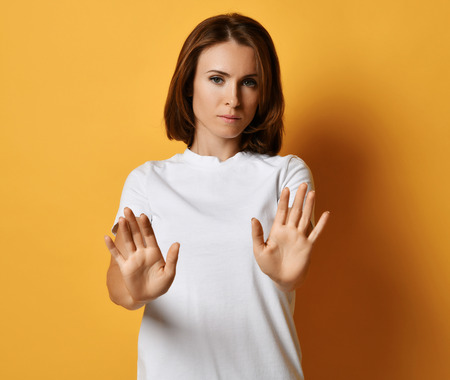 Concentrated looking woman in white t-shirt tries to stop something with her arms putted out. Shows Stop sign gesture on yellow background