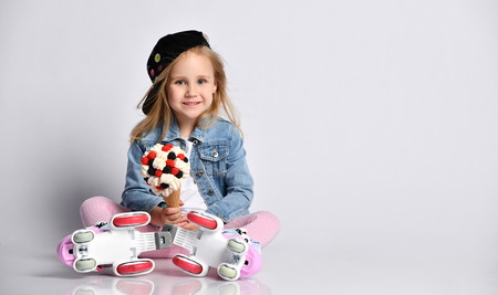 Little kid girl in roller skates sits on the floor holds a big and tasty ice-cream in waffles cone with topping. On white background with free text copy space Reklamní fotografie