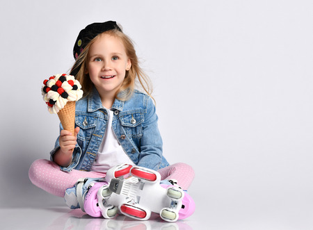 Little kid girl in roller skates sits on the floor holds a big and tasty ice-cream in waffles cone with tasty topping and listen or watch something funny, show for kids
