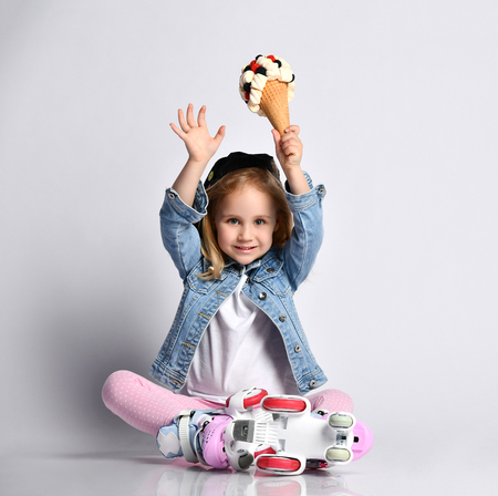 Happy blonde baby girl kid in roller skates sits on the floor and raises hands up with a big and tasty ice-cream in waffles cone with tasty topping marshmallows and berries Reklamní fotografie