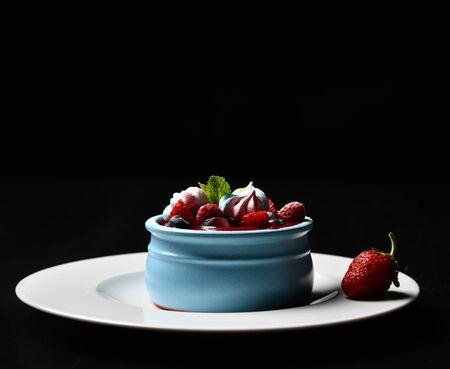 Strawberry desert for breakfast fresh ripe oatmeal blueberries and raspberries homemade yogurt pana cotta in blue jar on dark background. Healthy food concept