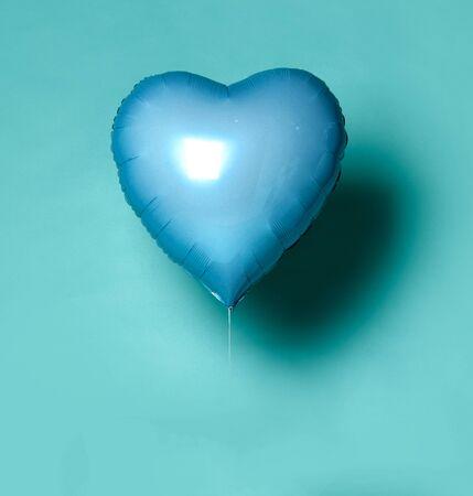 Single light blue big metallic heart balloon object for birthday on light blue mint background Stock fotó