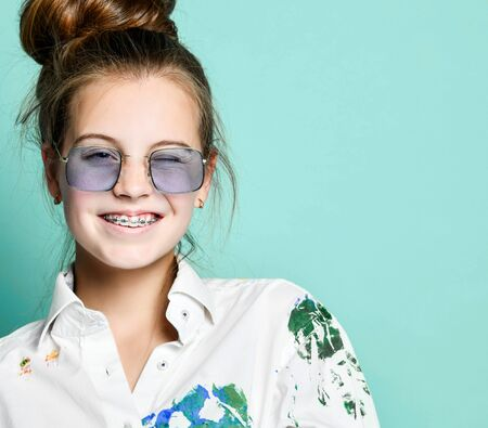 Portrait of smiling young woman girl with braces in white shirt with colorful paint stains and rectangular translucent glasses is frolic winking on gray background with copy space Фото со стока