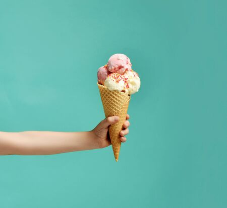 Baby kid hand holding big ice-cream in waffles cone on blue mint background Imagens