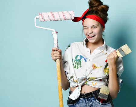 Portrait of smiling young woman pinup girl with braces in white shirt with colorful paint stains holding paintbrush and roller frolic winking on gray background with copy space