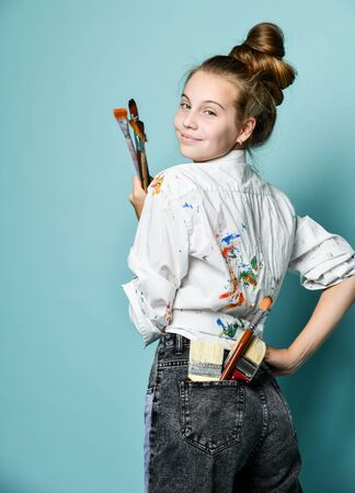 Portrait of artist decorator at work. Young woman in shirt with paint stains is standing back at the wall with a set of paintbrushes, looking over her shoulder at us