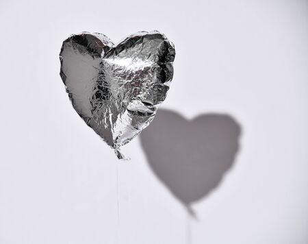 Party is over deflated silver heart balloon object for birthday party or love valentines day on white gray background with shadow Фото со стока