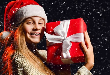 Happy smiling teenager girl with braces and in warm knitted sweater and christmas hat is holding her new year gift red box with ribbon at cheek under the snow on dark background Standard-Bild