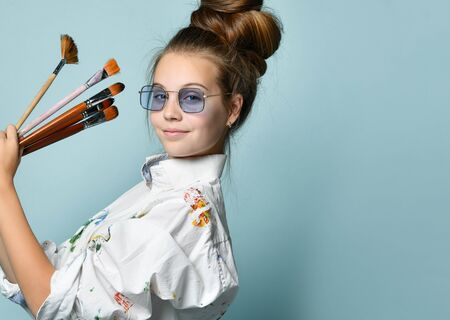 Portrait in profile of happy smiling young woman with hair tied in a bun in white shirt with colorful paint stains holding a set of brushes on gray background with free copy space Фото со стока