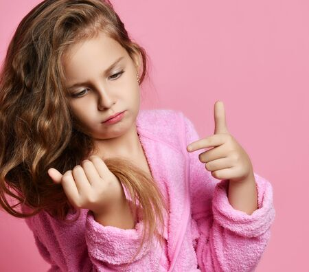 Baby girl or teen girl in spa salon is frightened with her hair style condition or something stuck or split ends of hair. Beauty concept on pink background Zdjęcie Seryjne