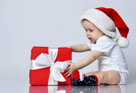 Infant baby boy toddler sitting in christmas cap and xmas present gift box playing white t-shirt on white background