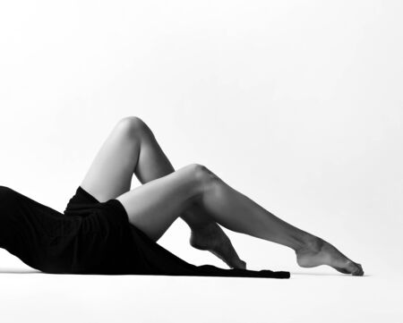 Closeup of a woman dancer ballerina perfect and naked legs lying on the floor in light black dress on white. Black and white