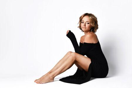 Une femme normale et amicale avec de courts cheveux blonds bouclés assise sur le sol en robe noire à épaules dénudées a glissé de ses genoux et avec un léger sourire sur blanc.