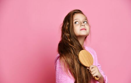 Young pretty girl combs her hair with a comb in the morning in her pajamas home bathrobe on pink background
