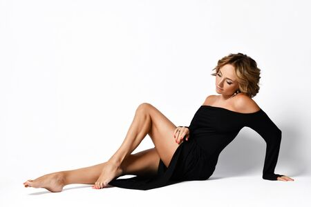 Delicate graceful woman in off shoulder light black dress is sitting sexual posing on the floor enjoying the view of her perfect thighs legs on white.