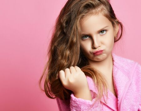 Baby girl or teen girl in spa salon is frightened with her hair style condition or something stuck or split ends of hair. Beauty concept on pink background Фото со стока