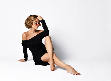 Emotional sensual pensive woman dramatic actress with her hand in her curly blonde hair sitting on the floor posing in off shoulder black dress slipped off her knees on white.