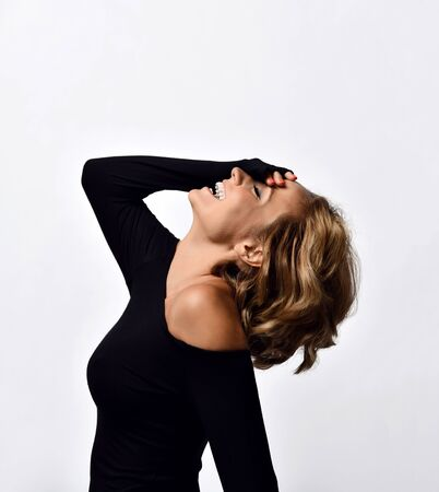 Portrait of loud laughing cheerful woman with short curly blonde hair in black tight off-shoulder dress standing with her palm covering her face and head back on white