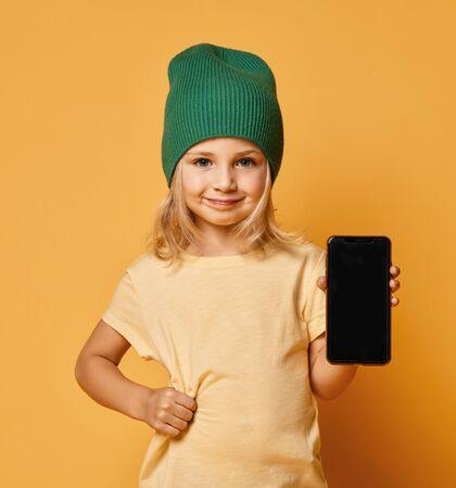 Sonriente niño niña gritando con sombrero de invierno moderno verde que muestra la pantalla en blanco del nuevo gadget de teléfono móvil popular sobre fondo amarillo claro