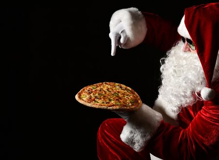 Merry Santa Claus is pointing down at big tasty pizza he is holding on his open palm, going to poke his finger, draw attention. New year and Merry Christmas fast food concept Stock Photo