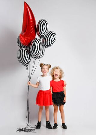 Happy kids girls in red and black skirts and white and red t-shirts are screaming singing songs playing celebrating having fun at party with stylish air balloons on white