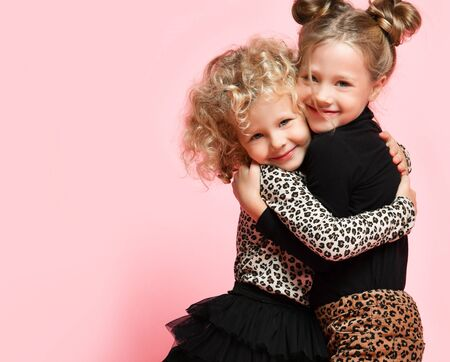 Two happy kids girls best friends sisters in leopard print clothes pants and sweater are hugging feeling love smiling on pink background with free copy space Archivio Fotografico - 134732732